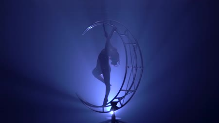tornász : Girl performs various hooks in a dark room on a device in the form of a spinning moon. Blue smoke background. Slow motion.Silhouette