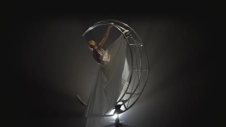 gracefully : Graceful acrobat in a white dress performs movements on a construction moon . Smoke background. Slow motion