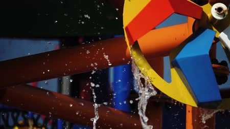waterslide : Multicolored circle in the form of a mill spinning with water .Slow motion. Close up