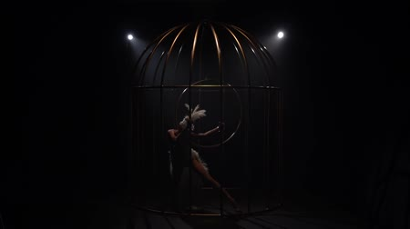 klec : Graceful girl gymnast riding a hoop in a cage on dark stage. Black background. Slow motion