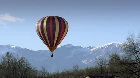 from air : hot air balloon in flight over mountains Stock Footage