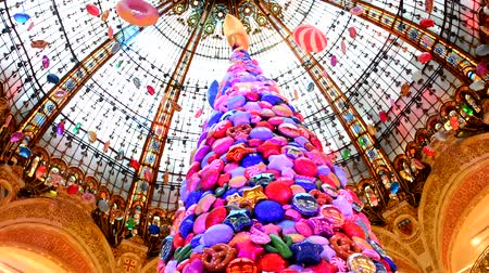 parisli : PARIS, FRANCE - NOVEMBER 20, 2017 Christmas tree with inflatable balls of sweets and cookies in the world famous store Galleries Lafayette Stok Video
