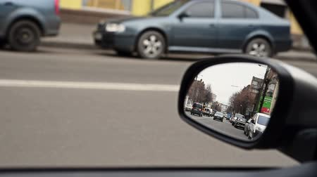 reflexão : View in rear view driving mirror on the city street Vídeos