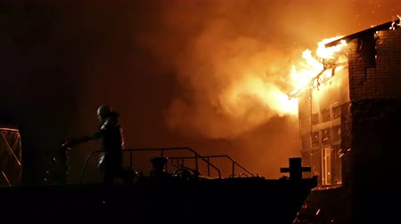 building heat : House building on fire at night. Inferno conflagration. Fireman fights fire.