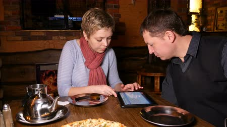 small businessman : Businessman and businesswoman business partners discussing startup using tablet pad and chatting in a restaurant cafe. 4K UHD video footage.