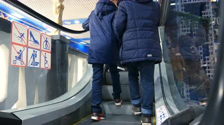 enduring : People are moving up on escalators at a shopping center. 4K UHD video footage.