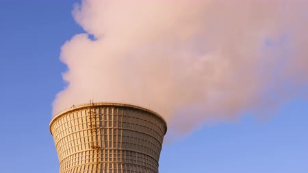 дымоход : Water cooling tower stack smoke over blue sky background. Energy generation and air environment pollution industrial scene. 4K UHD video footage. Стоковые видеозаписи