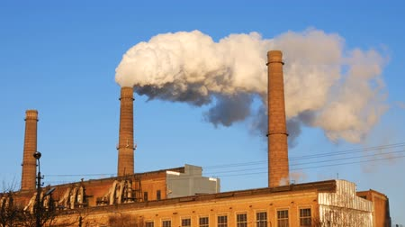környezetszennyezés : Factory plant smoke stack over blue sky background. Energy generation and air environment pollution industrial scene. 4K UHD video footage.