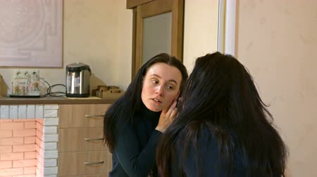 brincos : Beautiful brunette woman with long black silky hair puts on and wears earrings and smartens up in front of mirror in make-up dressing room. 4K UHD video footage.