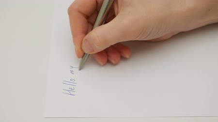сценарий : Female hand writes My dear friend on the sheet of white paper. Macro close-up shot. 4K UHD video footage.