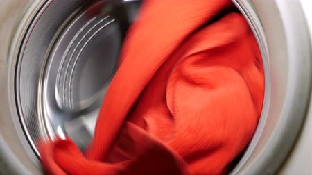 makineleri : Rotating washing or drying machine with red towel in a laundry. Household equipment and cleanliness hygiene housework concept. 4K UHD video footage.