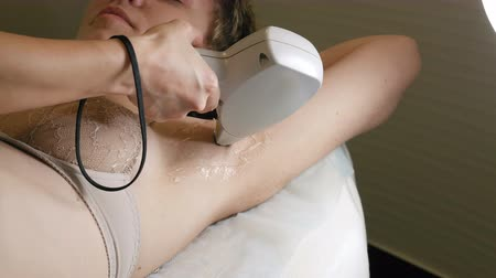 silme : Woman gets laser hair removal treatment underarm. Modern permanent epilation procedure. 4K UHD video footage. Stok Video