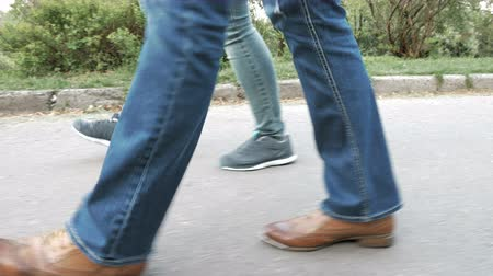 step : Womens feet on the sidewalk in shoes and sneakers trainers and jeans. Closeup tracking shot. 4K UHD video footage. Stock Footage