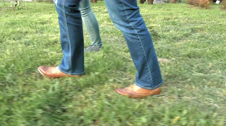 spor ayakkabısı : Womens feet on the green grass in shoes and sneakers trainers and jeans. Closeup tracking shot. 4K UHD video footage.
