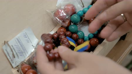 all ages : Several bracelets made out of wooden beads. Available in different sizes and colors. A customer is trying the bracelets on, best fit for all ages. 4K UHD video footage.