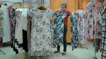 доля : A customer is in the process of finding the best suitable size for her. Dresses are available in various size, print and fabric. 4K UHD video footage. Стоковые видеозаписи