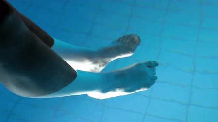 limpar : A woman is relaxing outside in the nighttime. She has her feet in the water in order to relax. Pool must be clean and well taken care of. Vídeos
