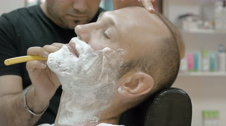 borbély : The barber is shaving his client in old fashion manner. Single blade shave gives the best result. Grooming is necessary for men and woman. Stock mozgókép