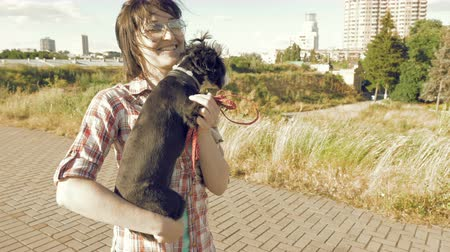 dog sitter : Young woman lovely holding on hands and caressing little cute dog outdoors on city background. Enjoying of active healthy walk with pet at summer sunny day.