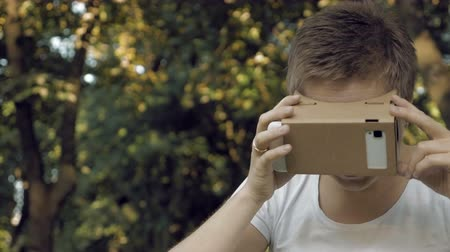 ciberespaço : Woman explores virtual reality using cardboard VR glasses. Augmented reality quickly comes in human lives. VR mounted displays helmets and glasses are the most popular devices for playing AR games. Vídeos