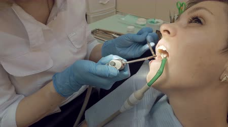 yenirce : Woman at the dentist clinic office gets dental medical examination and treatment. Close up shot. Odontic and mouth health is important part of modern human life that dentistry help with.