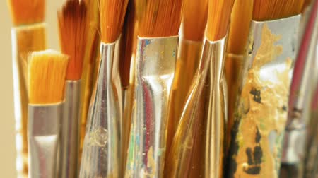 artista : Artist paintbrushes. Set of different artist paint brushes in old crock close-up. Art studio concept. Selective focus footage with shallow DOF.