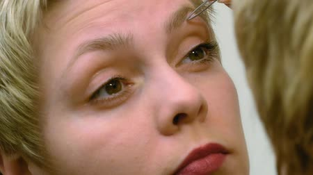 plucks : Blond short hair woman plucks and pulls her eyebrows out in front of mirror. Beauty and makeup concept. Stock Footage