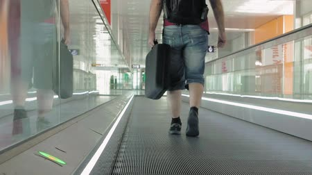 mozgólépcső : A person is walking on a moving pathway in the airport. It is used to transport people across hall. Travolator makes is easy to carry heavy luggage. Stock mozgókép
