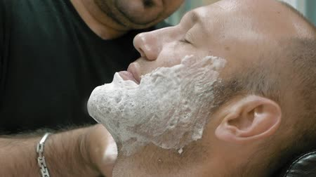 barbear : A man is sitting at a barbers shop to get groomed. The barber is lathering on the shaving cream on his client with a soft blending brush.