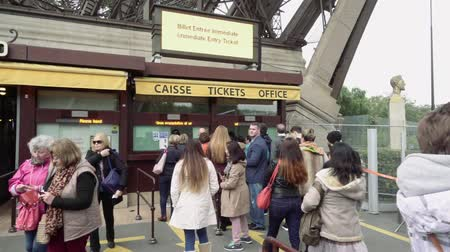 kuyruk : Paris, France - October 15, 2016: Tourists stand in queue to Eiffel Tower ticket office on cloudy day. People flock to enter of well-known city landmark. Slow motion. Camera stays still.