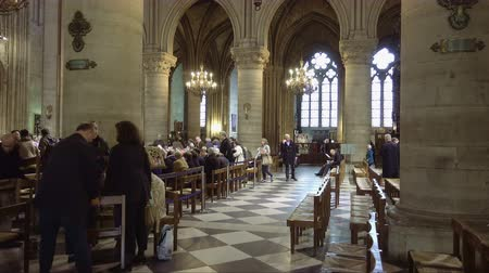 церковь : Paris, France - October, 14, 2016: Notre Dame de Paris cathedral interior with prayers and tourist visitor getting ready to listen a sermon from a priest.