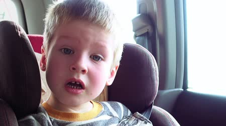 ülés : Little cute boy in a car seat looks out the window and yawns. Pure emotions over child face. Stock mozgókép