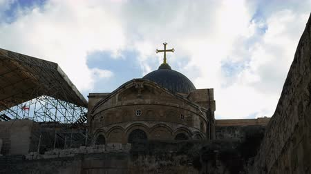 dolorosa : Golden cross over Temple of the Holy Sepulcher church in Jerusalem timelapse. The Holy Sepulchre Church is the most sacred place for all Christians in the world.