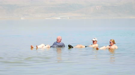 filistin : Dead Sea, Israel - May 22, 2017: People are bathing and swimming in the Dead Sea. The salinity of the dead sea water makes people floating in water. Dead sea is located between Jordan and Israel.