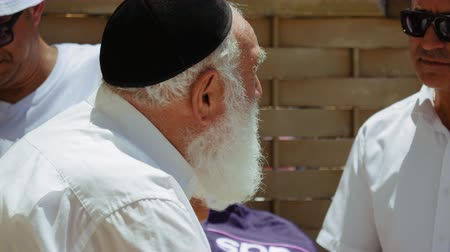 israelite : Jerusalem, Israel - May 25, 2017: Jewish senior old man with beard talks with emotions and expression to another man outdoors. All jews are used to wear the kippah or yarmulke small hat.