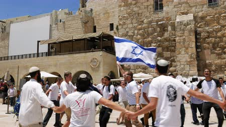 Jerusalem, Israel - May 25, 2017: Jews dancing in a round with flag celebrating the Jerusalem Day at Western Wall (Wailing Wall, Kotel) the most sacred place for all jews and jewish in the world.