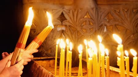 dolorosa : Jerusalem, Israel - May 25, 2017: Prayers lighting candles in the Holy Sepulcher Church in Jerusalem. The Holy Sepulchre Church and Empty Tomb the most sacred places for all Christians in the world. Stock Footage