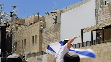 israelite : Jerusalem, Israel - May 25, 2017: Jews dancing in a round with flag celebrating the Jerusalem Day at Western Wall (Wailing Wall, Kotel) the most sacred place for all jews and jewish in the world.
