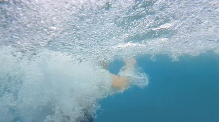 plunging : Running into swimming pool from water slide in slow motion. Underwater shot of person plunging down at high speed making bubbles waves and splashes. Water slides are pleasant recreational sites. Stock Footage