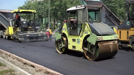 macadam : Kiev, Ukraine - June 19, 2017: Road construction. Workers applying new hot asphalt using road construction machinery and power industrial tools. Roadworks repaving process.