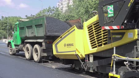 macadam : Kiev, Ukraine - June 19, 2017: Road construction. Applying new hot asphalt using road construction machinery and power industrial tools. Roadworks repaving process.