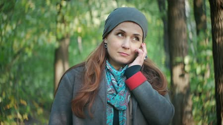 telefon : Attractive hair talking on the phone while standing in the autumn forest Stock mozgókép