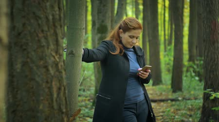 correspondência : girl stands near the tree and writes sms on the phone