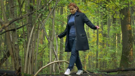 balanceamento : girl in a blue turtleneck and red hair in white sneakers, goes along the log of a fallen tree