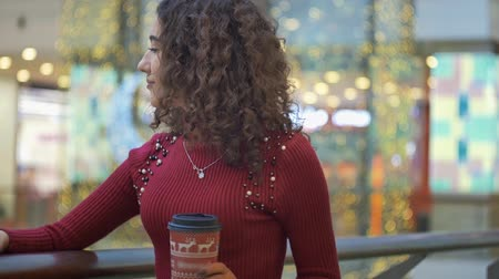 que vale a pena : young girl in a red sweater is standing with a glass of coffee and smiling