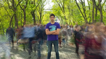 awesome : The man stand in the ghost-like crowd flow, on background green trees . Time lapse. The camera is approaching