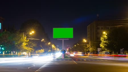 billboards : A billboard with a green screen on a background of city traffic with long exposure. Time Lapse. The camera moves away Stock Footage