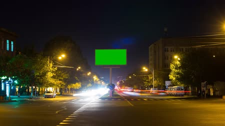 publicity : A billboard with a green screen on a background of city traffic with long exposure. Time Lapse. The camera is approaching