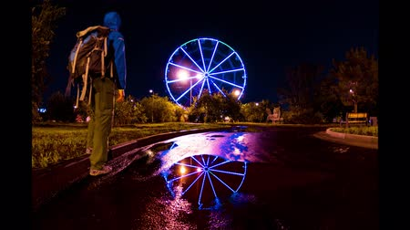 münchen : man stands in front of a glowing illumination by a ferris wheel, reflected in a puddle. Time lapse