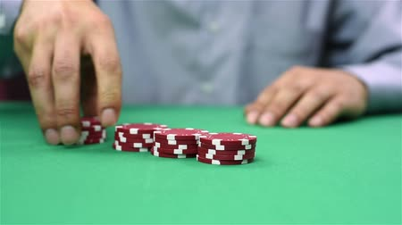 покер : dealer collects red poker chips from the table